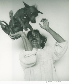 A black and white photograph of the artist Francisco Toledo in a white button down shirt, throwing a small Itzcuintli dog into the air