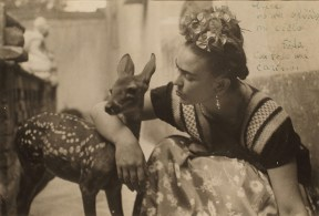 A black and white photograph of Frida Kahlo with her pet deer.