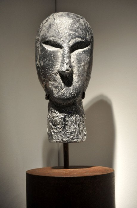 A cast glass sculpture of a silver head with stylized features