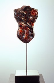 A cast glass sculpture of a human torso, in red glass and pigment