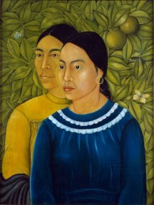 Two women dressed in blue and yellow seated in front of foliage and fruit