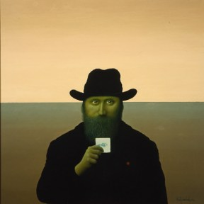 A man wearing a black coat and hat stands in front of a horizon, holding a small white card.