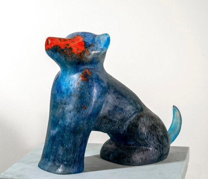 A glass sculpture of a seated blue wolf, with a red face