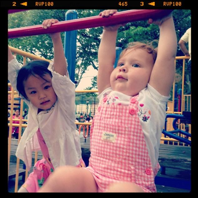Cristina jugando en el parque, a su lado una niña china.
