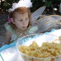 Esta pequeña hada aprovecha para comer papas fritas antes de que lleguen los invitados.