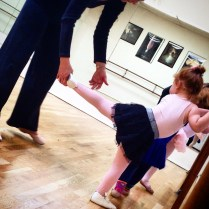 La maestra corrigiendo su postura.