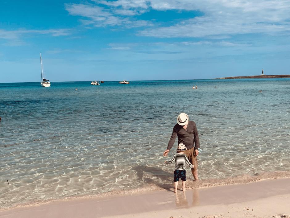 Papi und Baby am Strand in Menorca. Beide tragen einen Sonnenhut und stehen im Wasser