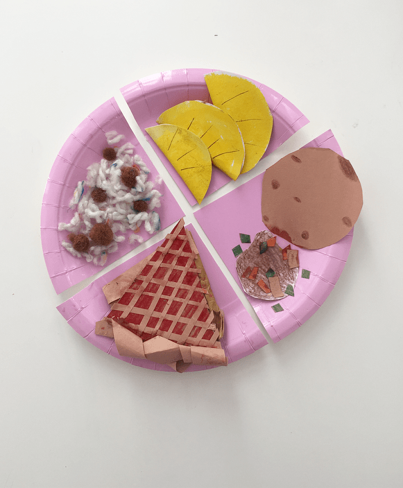 Crafted foods on a paper place including pie made out of card.