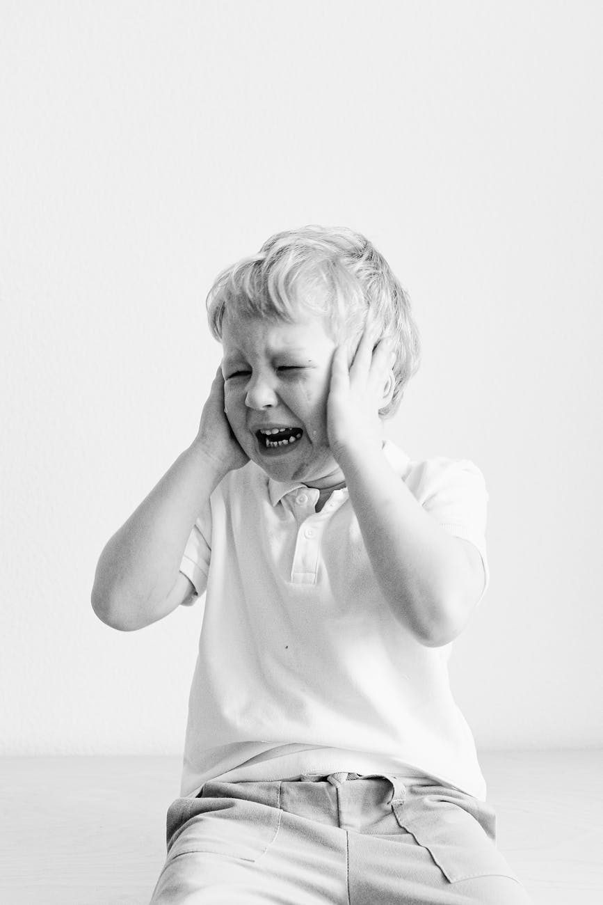 grayscale photo of a boy crying