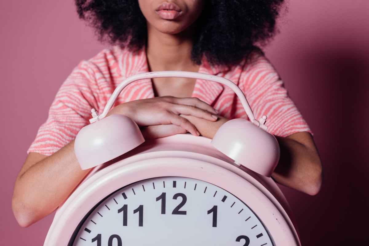woman on big pink alarm clock
