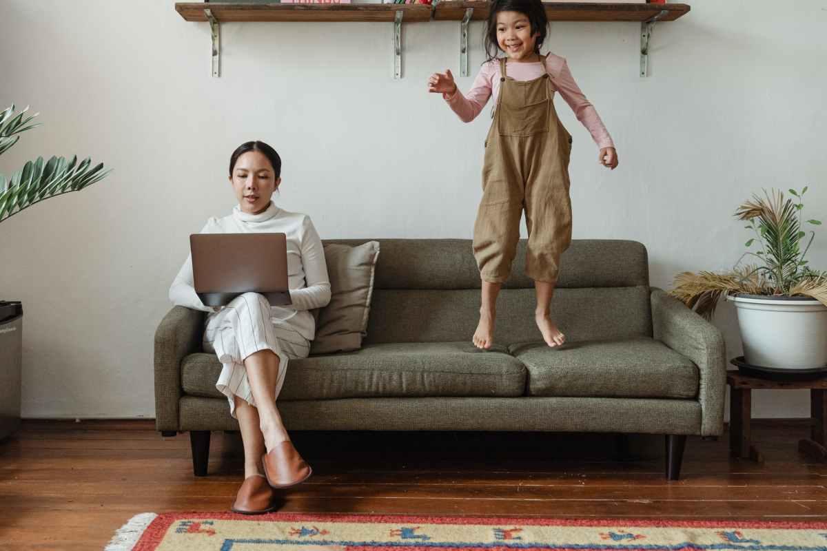 focused mother working on laptop near disturbing daughter