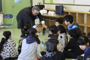 社長が生徒に溶接した鉄板を回覧しています