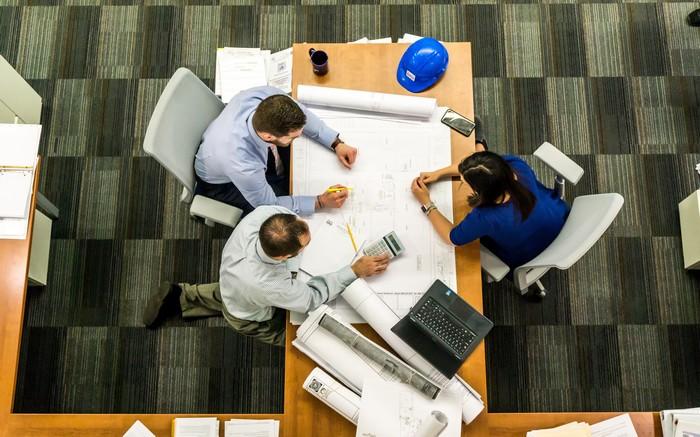 photo d'une equipe de 3 personnes autour d'une table pour un projet