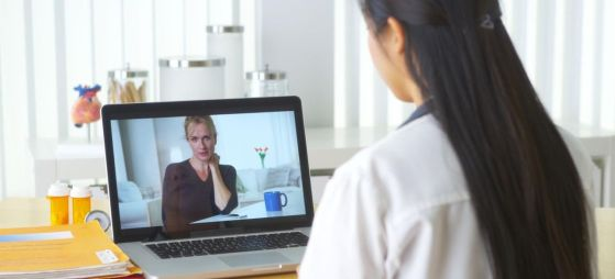 Chinese doctor video chatting with elderly patient