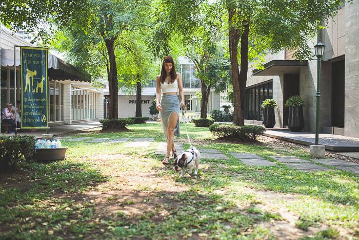 girl walking her dog at ozono park in bangkok