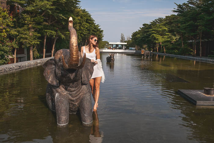 girl standing next to elephant statue