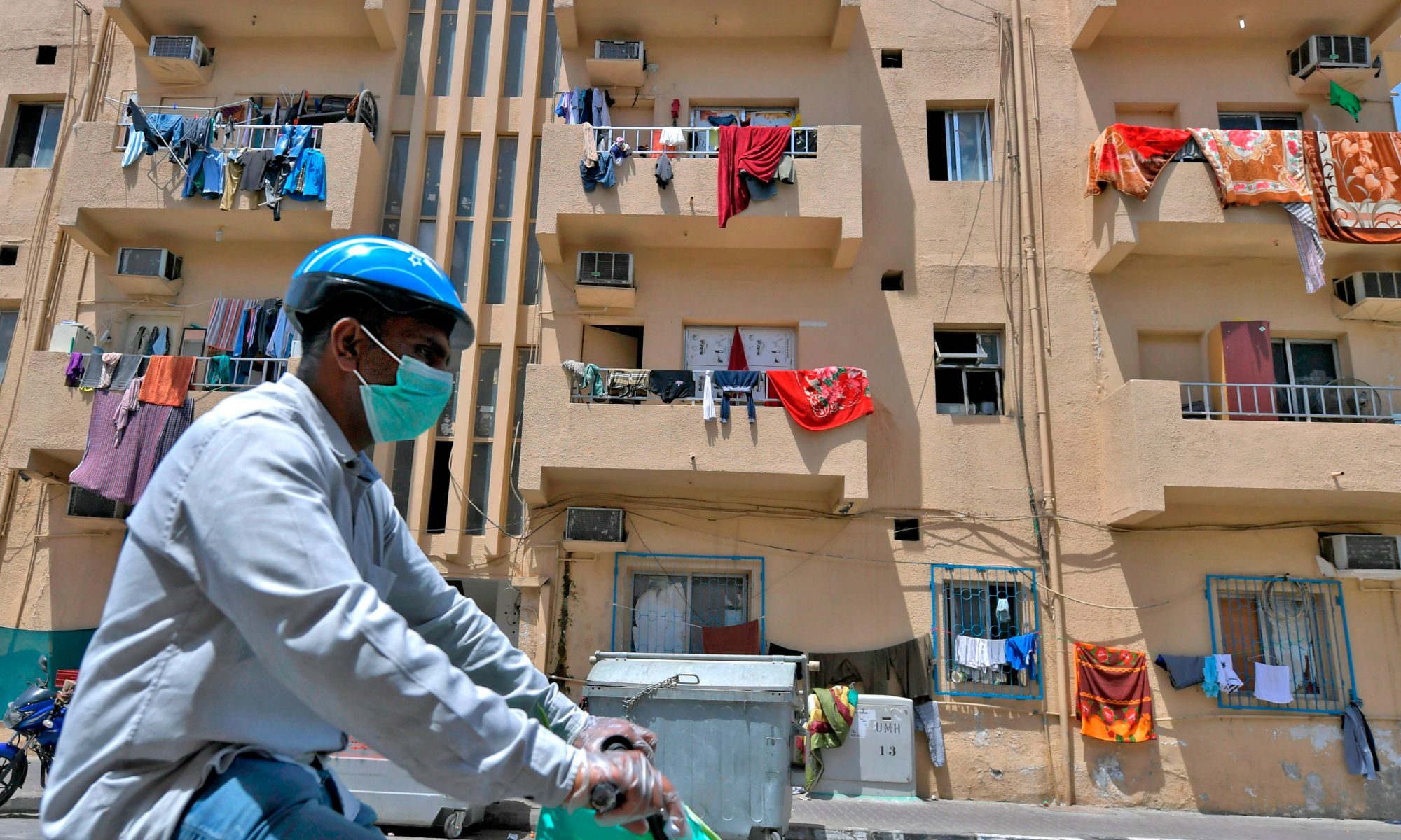 Migrant worker riding bicycle in mask.