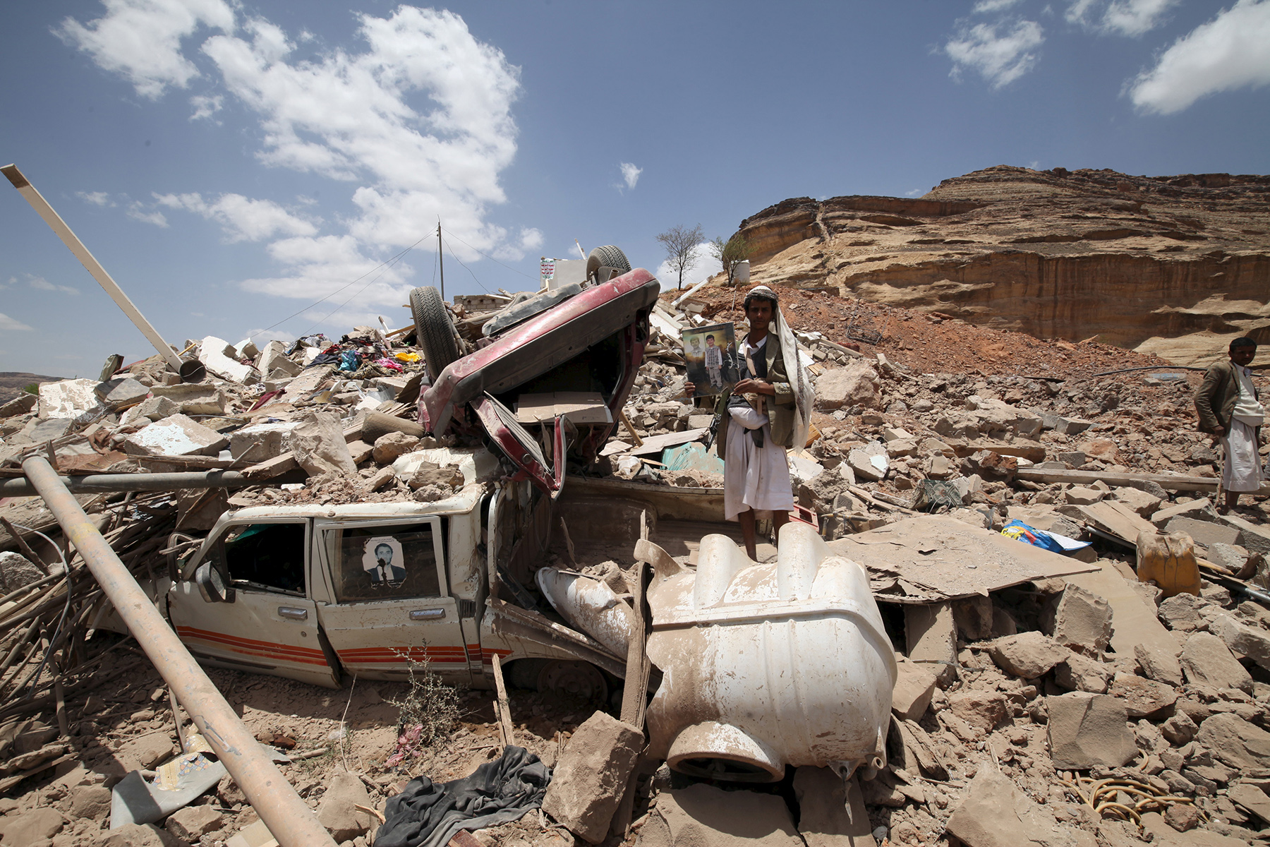 A Houthi militant stands amidst debris from a house of a Houthi leader which was destroyed by a Saudi-led air strike, near Sanaa
