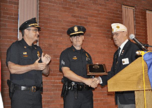 Sgt. Brandon Murphy, Center, receives award from American Legion member. Chief David Mara, left, applauds.
