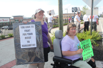 Hollie Kraatz, left, and sister Leah Kraatz, hold signs in support of ousted CEO Arthur T. DeMoulas.