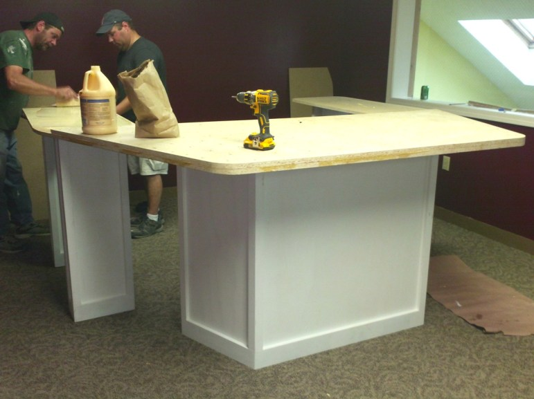 Jeff Brockstead and Bill Oxley work on the new eight-person interview table as part of the major expansion for WLMW and the Girard at Large show.