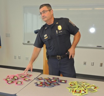 """Chief David Mara stands beside a table of confiscated """"spice."""""""