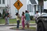 Neighbors watch from across the street as police tape off Kennard Street.