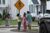 Neighbors watch from across the street as police tape off Kennard Street.