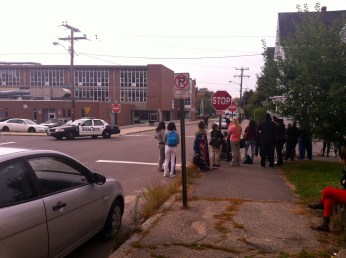 Neighbors stand behind police tape outside West high School during lockdown.