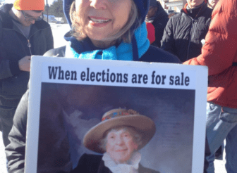 A NH Rebellion walker in Merrimack holds a poster featuring Granny D.