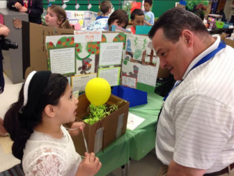 School board member John Avard talks with a student about the Gator Zoo.