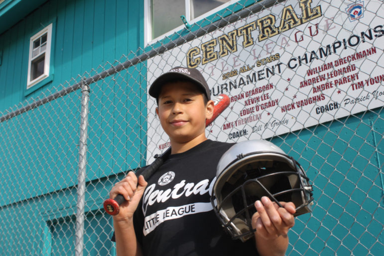 Michael Negron, 12, shows off some of the donated equipment from Project Play. He has been playing baseball in Manchester since he was 5.
