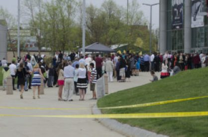SNHU graduation attendees waiting to get inside the Verizon, around police tape.