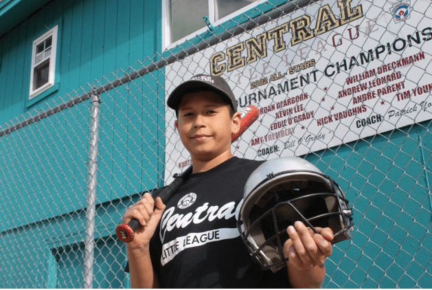 Michael Negron, 12, shows off some of the donated equipment from Project Play, which has helped supplement the team's equipment budget.