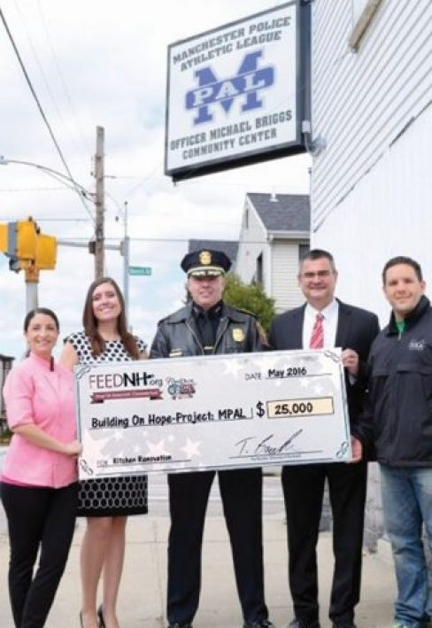FEEDNH.org donates $25,000 to the Building On Hope project for the Manchester Police Athletic League. Shown left to right: Chef Nicole Barreira, Great NH Restaurants, Tanya Randolph, FEEDNH.org, Manchester Police Chief Nick Willard, Chief David Mara, and Police Officer John Levasseur. The funds are earmarked for the buildings kitchen renovation.