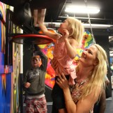 Officer Shannon Jackson gives daughter Alessandra a lift to reach the punching bag.