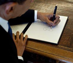 Barack Obama, presidente degli stati uniti mancino, firma un documento alla casa bianca