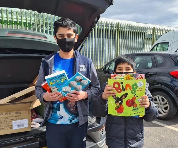Two children holding various books