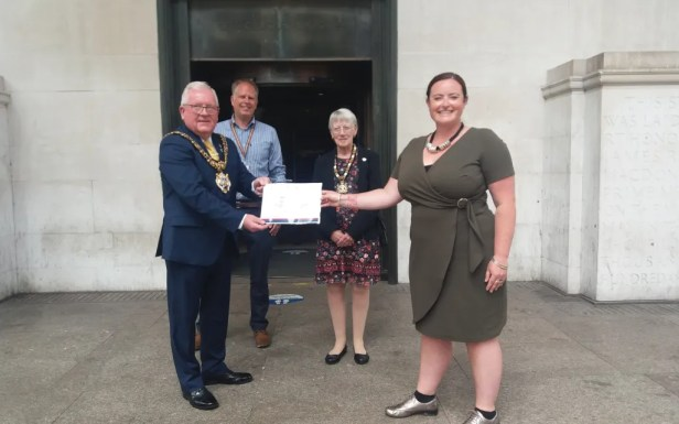 Lord Mayor Councillor Tommy Judge receiving the award from Liz Hubberd from Manchester City of Sanctuary outside Central Library.