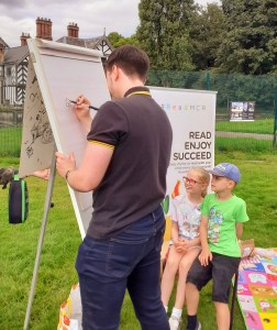 Ian Morris Drawing on a flip chart with two children watching.