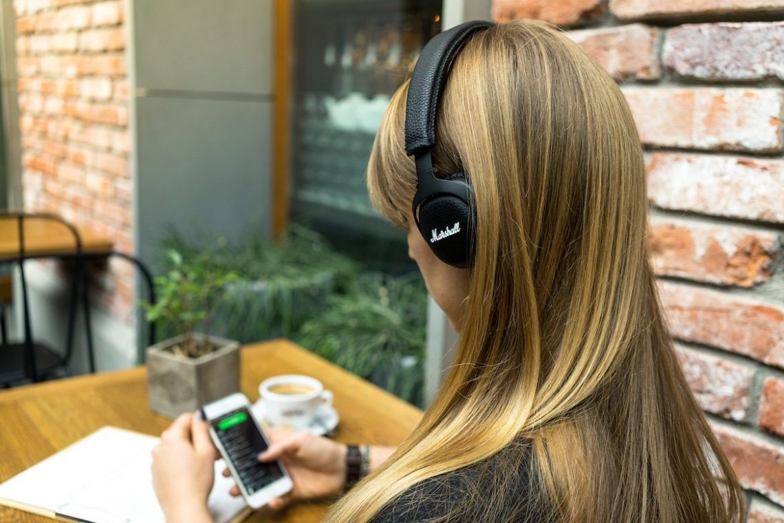 Marshall Kopfhörer Frau blonde Haare Smartphone Tisch Kaffee