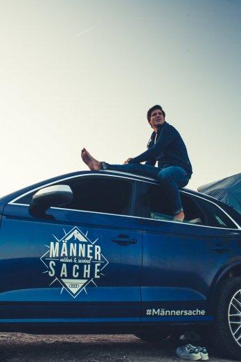 Adrian sitzt auf Audi SQ5 Dach