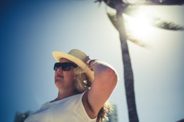 Blonde Frau mit Sonnenbrille und Hut in der Karibik