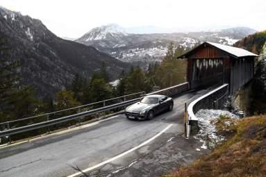 Brücke Holzhaus Strasse Berge Kurve Sportwagen Scheinwerfer