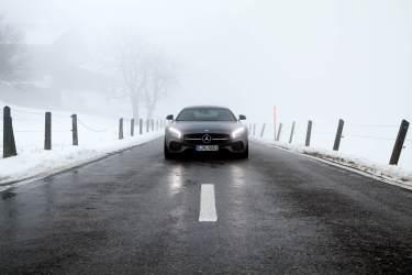 Nebel Scheinwerfer Lichtkegel Auto Grau Zaun Schnee Berge