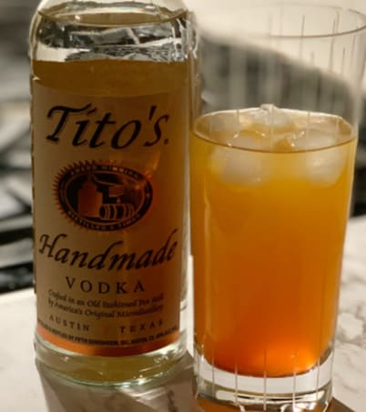 Tito's Vodka bottle beside mixed drink