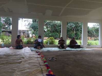 Gathering on woven mats before a community cooking demonstration