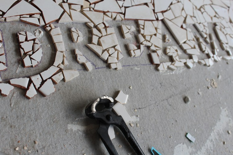 The making of a large mosaic commissioned by Darley Avenue Sure start emblazoned with the words DREAM, PLAY & LEARN, children and parents contributed to the mosaic.