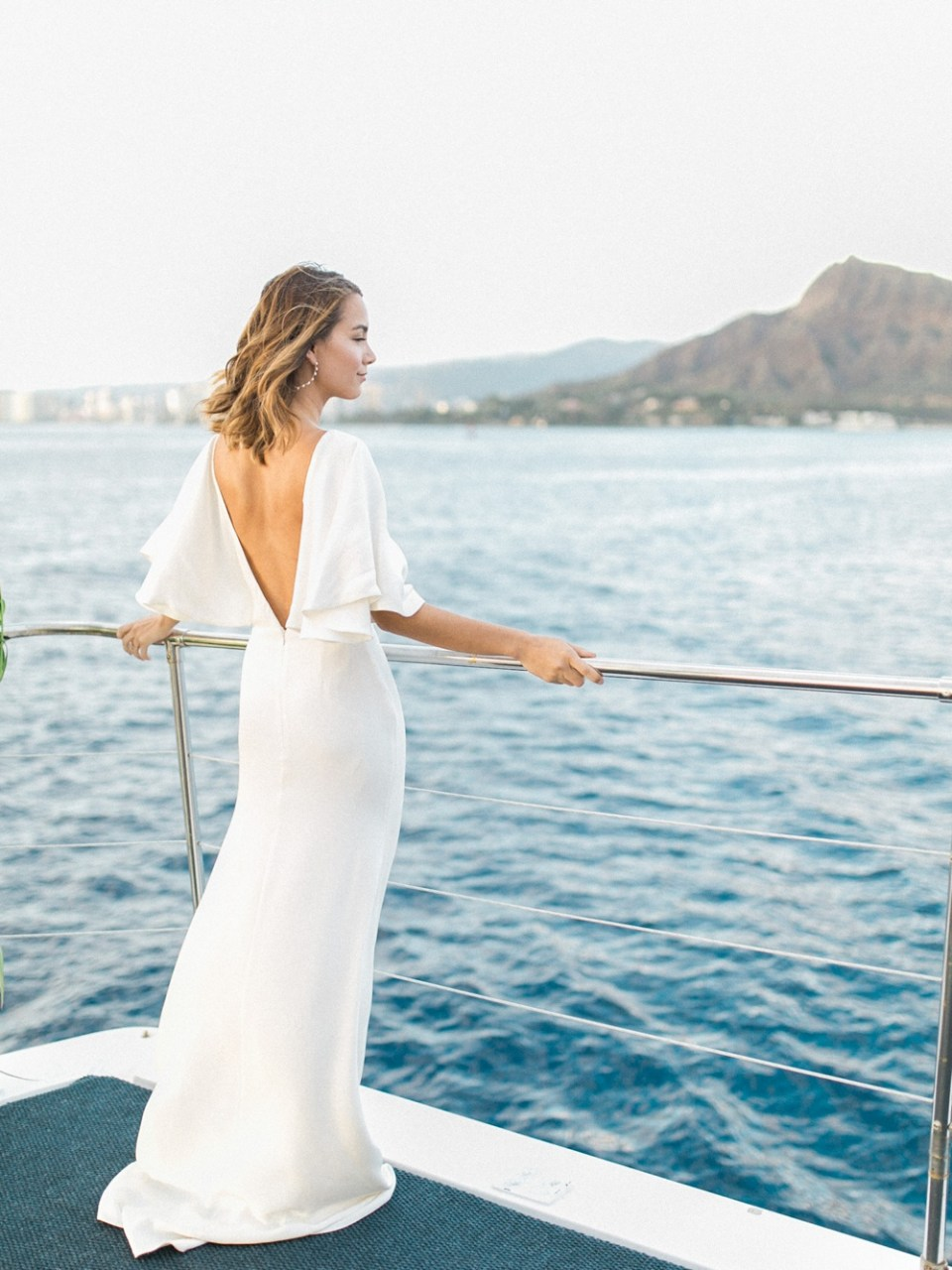 Woman taking in views on yacht in Sarah Seven dress
