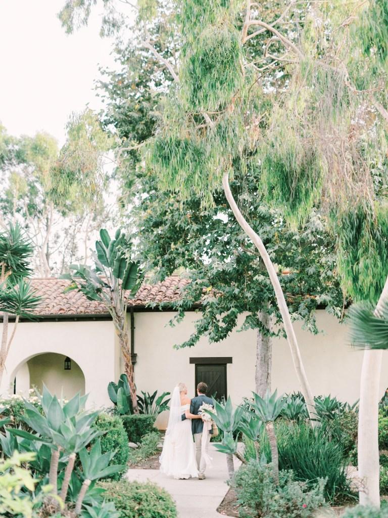 Beautiful Couple Walking In Landscaped Gardens At Estancia La Jolla Wedding Venue In San Diego
